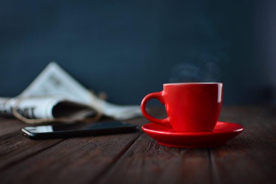 Eine Zeitung, ein Handy und eine rote Tasse stehen auf einem Holztisch.