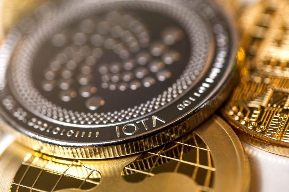 Eine IOTA-Münze liegt auf eine Haufen anderer goldener Münzen.