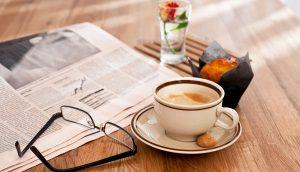 Eine Zeitung, eine Brille, eine Kaffeetasse samt Untertasse, ein Muffin und eine Blume stehen auf einem Holztisch.