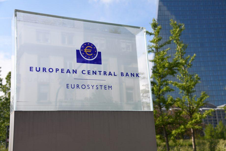 Eine gläserne Tafel mit dem Logo der EZB drauf. Daneben ist der Banken-Tower der Zentralbank.