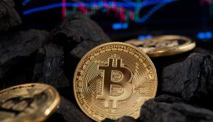 Bitcoin-Münzen und Kohle vor Chart-Hintergrund