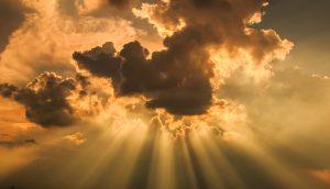 Lichtstraheln durchbrechen eine Wolke.