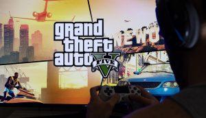Ein Spieler sitzt vor einem Bildschirm auf dem GTA V zu sehen ist.