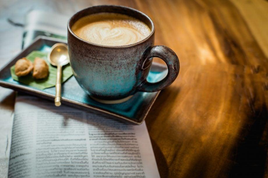 Eine Tasse Kaffee steht auf einem Untersetzer, der auf einer Zeitung steht, die auf einem Holztisch liegt.