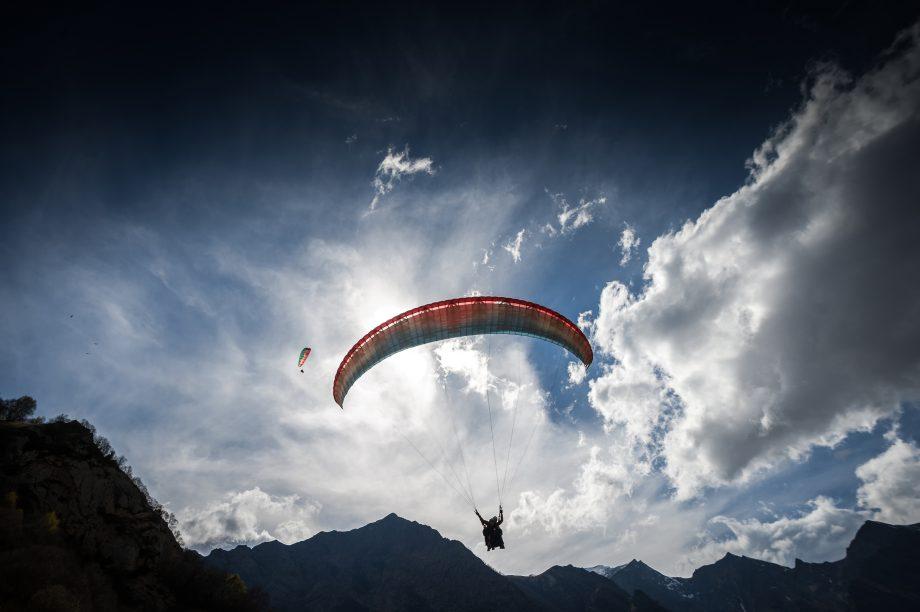 Ein Paraglider fliegt knapp über einen Berg.