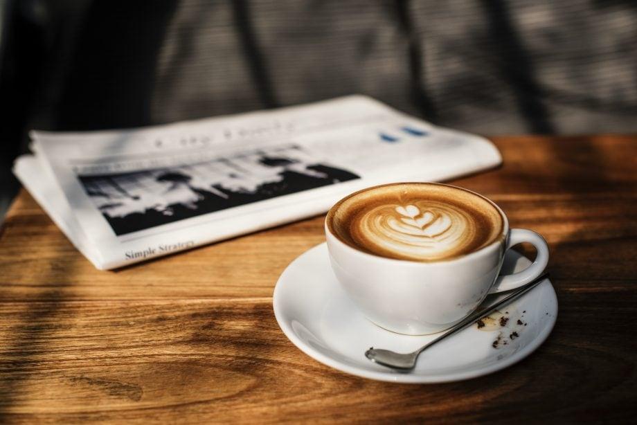 Eine Zeitung und eine Tasse Kaffee stehen auf einem Holztisch.