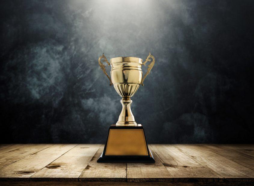 Ein goldener Pokal steht im Scheinwerferlicht.