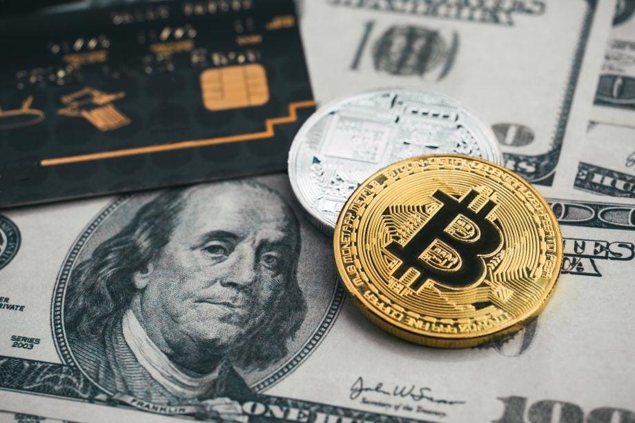 Eine Debitkarte liegt neben zwei Krypto-Münzen auf einem Hundertdollarschein.