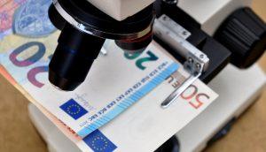 Geld bzw. Euroscheine liegen unter einem Mikroskop