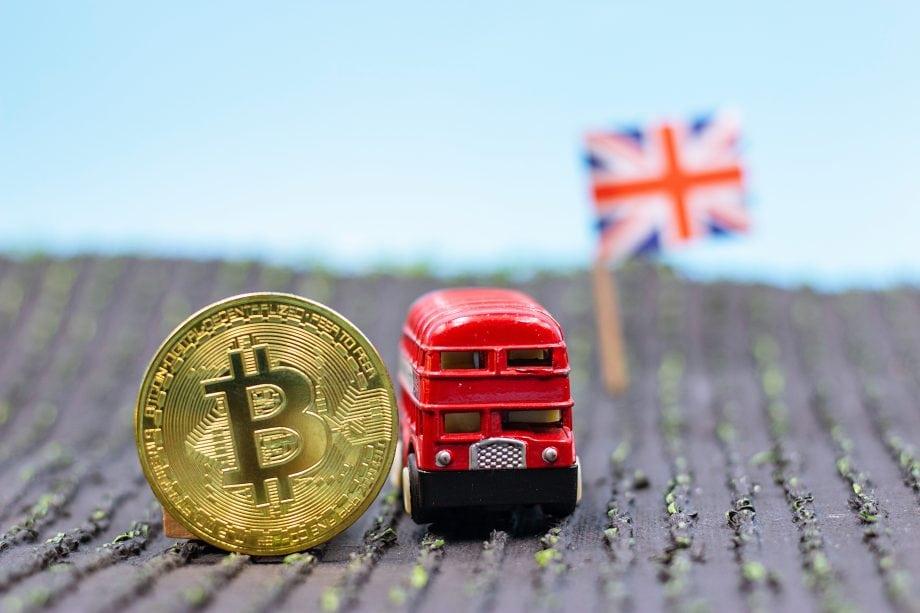 Bitcoin-Münze neben einem Londoner Spiezleugbus, im Hintergrund die Großbritannien-Flagge