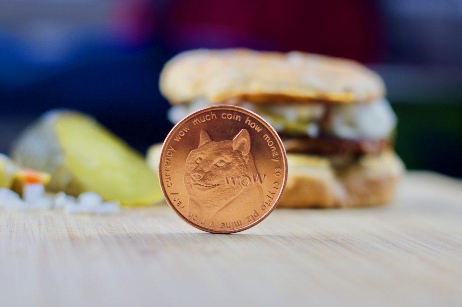 Dogecoin-Münze, im Hintergrund ein Burger