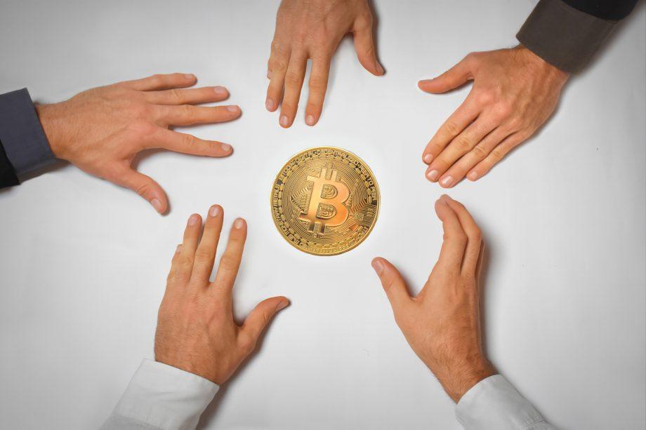 Fünf Hände greifen nach einem Bitcoin –(Symbolbild institutionelles Krypto-Engagement)