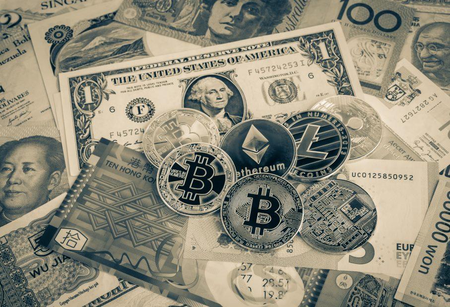 Ein paar US-Dollar-Noten liegen neben diversen Krypto-Münzen.