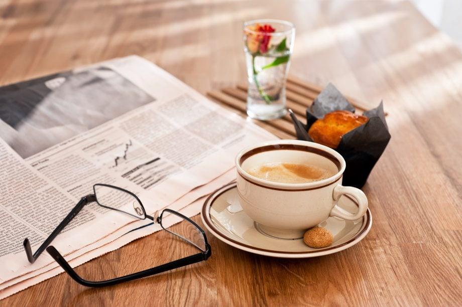 Eine Brille, eine Zeitung, eine Kaffeetasse, ein Muffin und eine Blume stehen auf einem Holztisch.