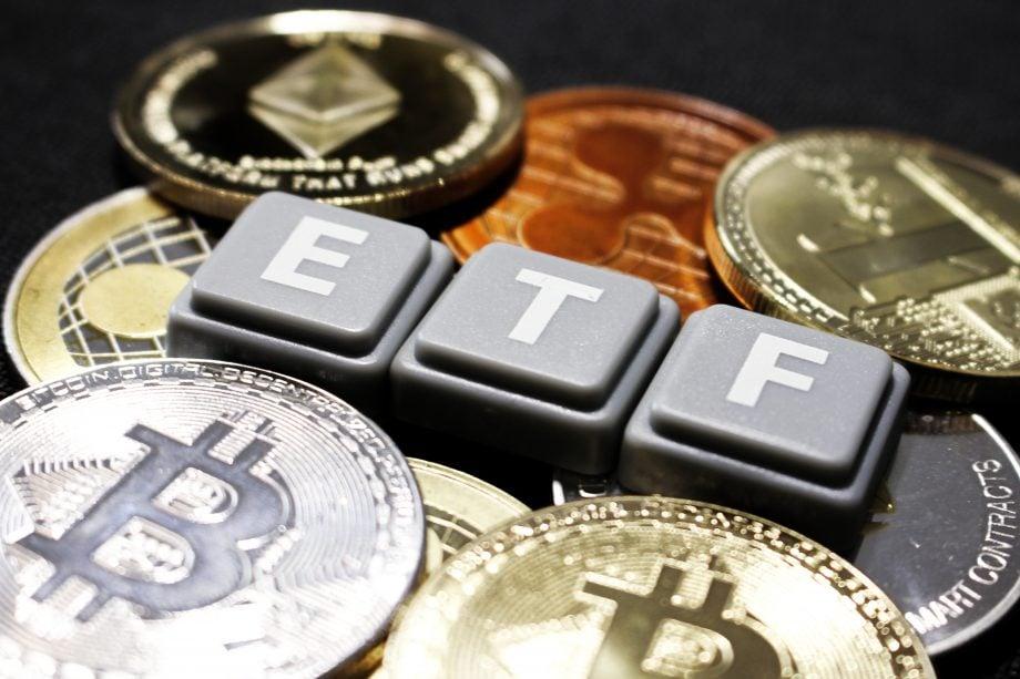 Mehrere Krypto-Münzen auf einem Tisch. In der Mitte steht in Großbuchstaben