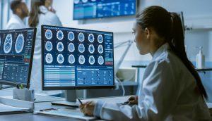 Wissenschaftlerin sitzt vor Computer mit verschiedenen Medizindaten drauf.
