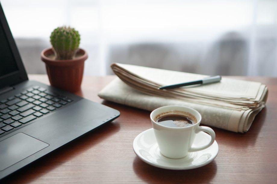Zeitung, Kaktus, Laptop und Kaffeetasse stehen auf eine Holztisch.