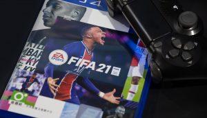 Das Cover von Fifa 21, daneben ist ein PS4-Controller.