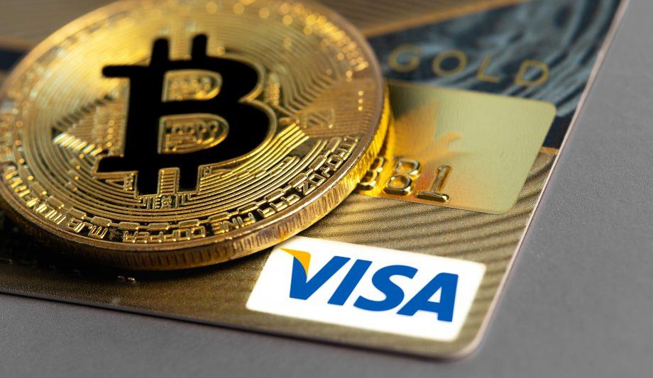 Ein Bitcoin liegt auf einer Visa-Karte