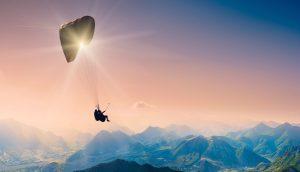 Ein Paraglider fliegt über die Berge