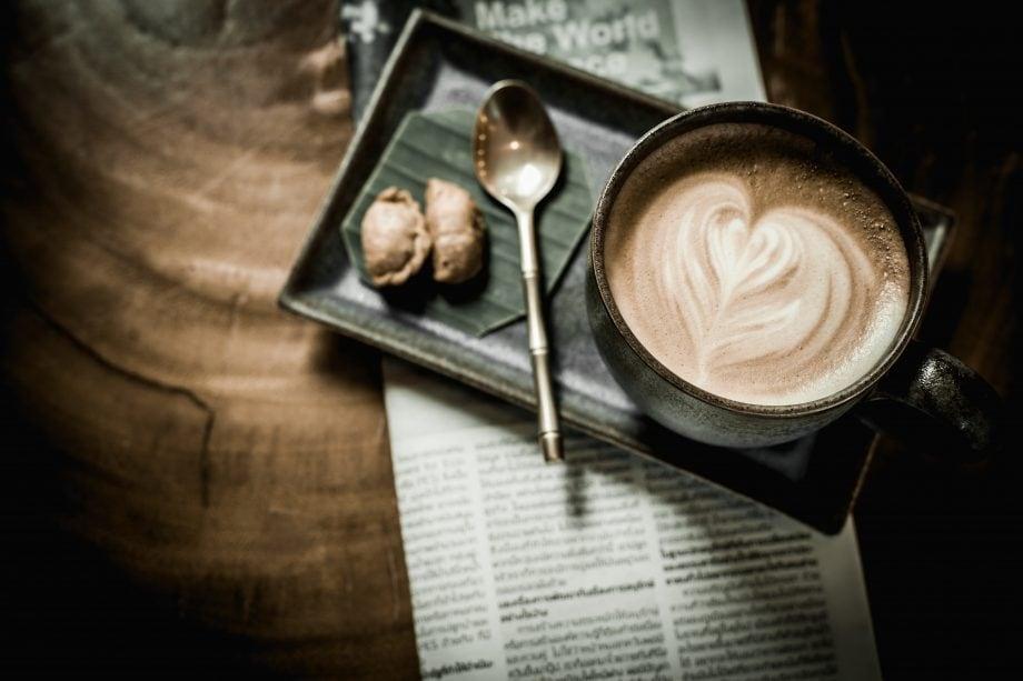Eine Kaffeetasse steht auf einem Tablett mit Löffel und Keksen, das auf einer Zeitung steht.