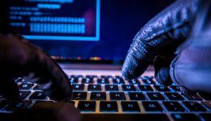 Ein Cyberkrimineller tippt auf einer Tastatur.