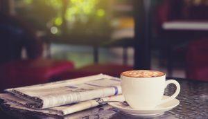 Eine Zeitung lieg neben einer Tasse Kaffee auf einem Steintisch. Dahinter fällt Licht durch ein Fenster in den Raum.
