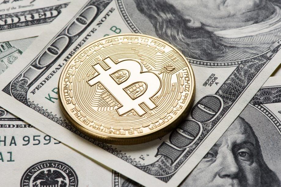 Ein Bitcoin liegt auf einer 100-US-Dollar Note.