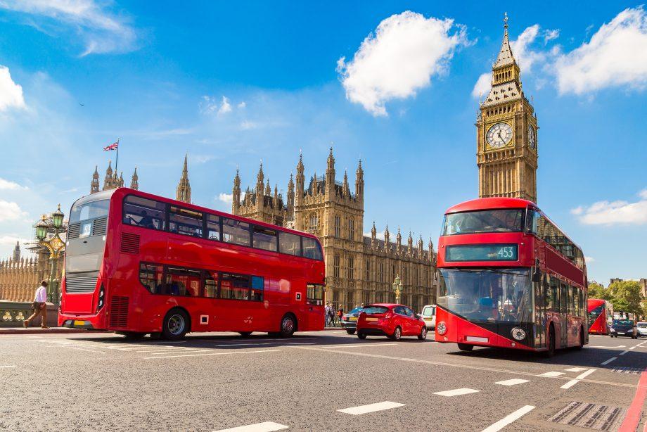 Zwei Busse in London vor der Westminster Abbey und dem Big Ben.