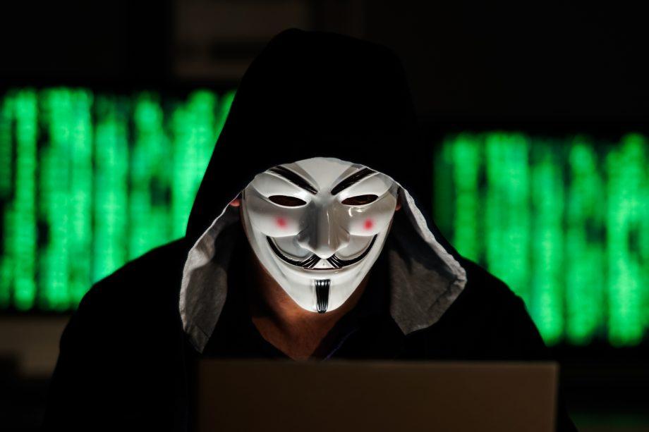 Person im schwarzen Kapuzenpullover sitzt mit Guy Fawkes Maske vor einem Laptop.