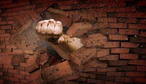Faust durchbricht Ziegelmauer.