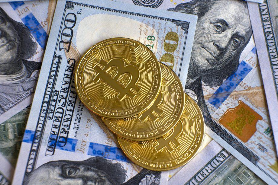 Bitcoin-Münzen liegen auf Dollarscheinen