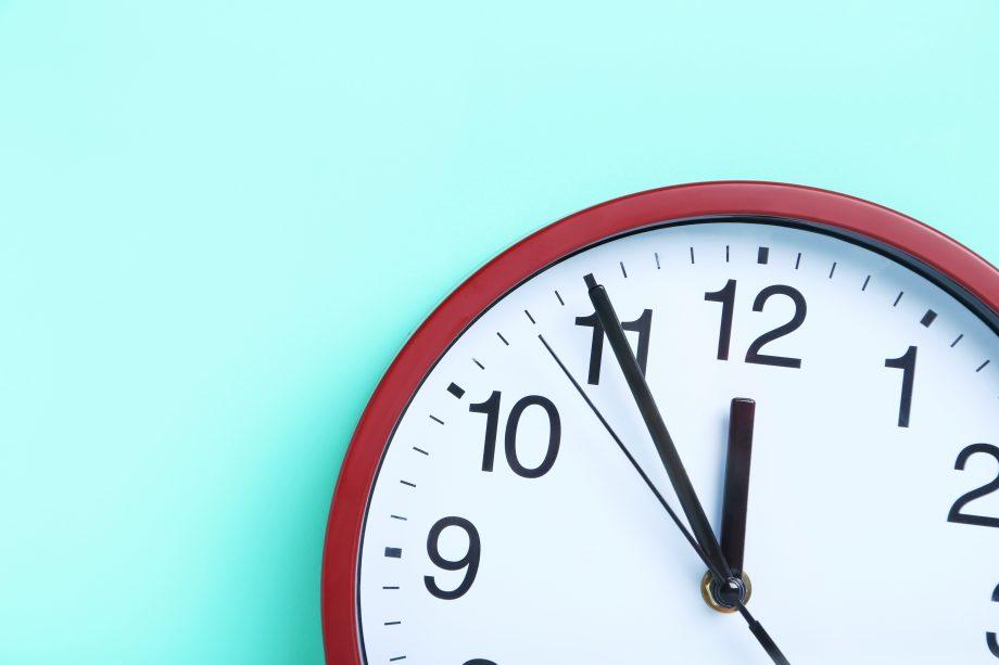 Eine Uhr vor einem türkisen Hintergrund