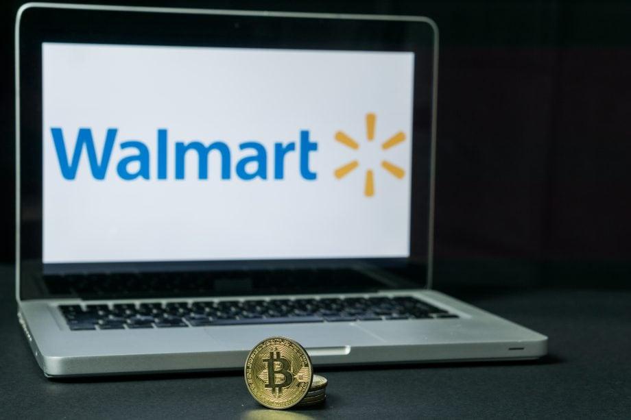 Bitcoin-Münze liegt vor einem Laptop mit Walmart-Logo