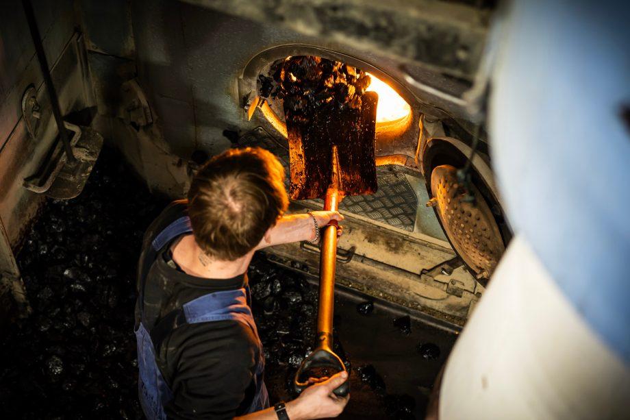 Mann schaufelt Kohle in den Ofen eines Boots