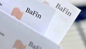 Das Logo der BaFin auf mehreren Papierseiten.