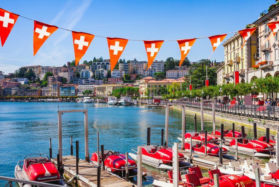 Dargestellt ist eine wunderschöne Schweizer Stadt am Wasser, geschmückt von 9 Schweizer Flaggen