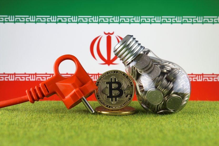 Eine Bitcoin-Münze steht neben einem Ladekabel und einer mit Münzen gefüllten Glühbirne