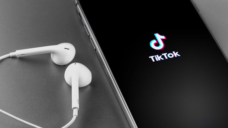 Weiße Kopfhörer liegen neben einem Smartphone mit TikTok-Logo.