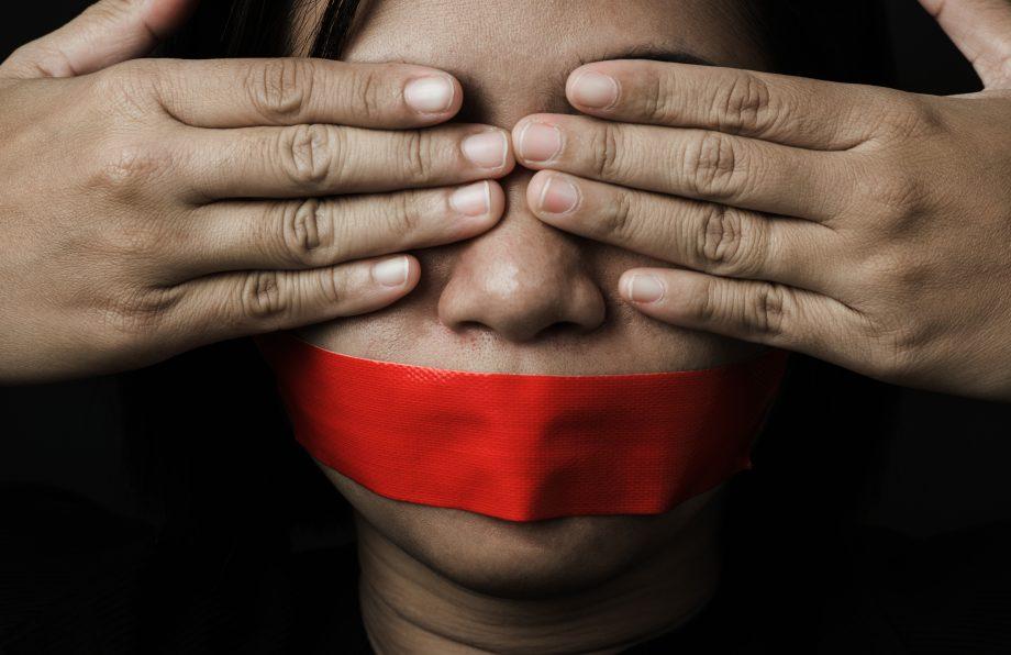 Frau mit verschlossenen Augen und abgeklebten Mund.
