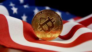 Eine Bitcoin-Münze liegt auf der US-Flagge.