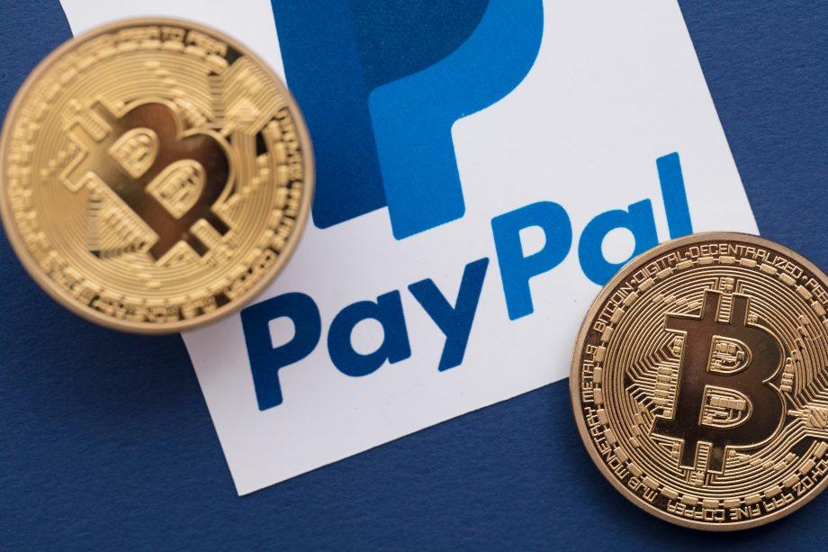 Zwei Bitcoin-Münzen neben dem PayPal-Logo