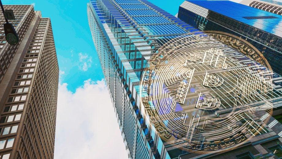 Ein gläsernes Hochhaus. Daneben ist eine Bitcoin-Münze.