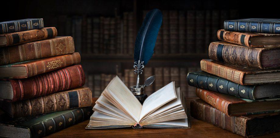 Aufgeschlagenes Buch liegt auf einem Tisch, umringt von Bücherstapeln