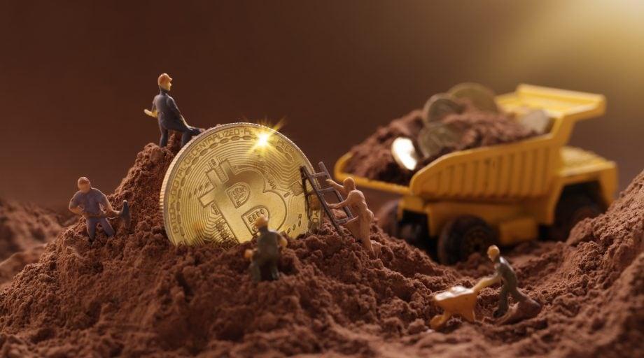 Bitcoin Münze wird von kleinen Figuren ausgegraben