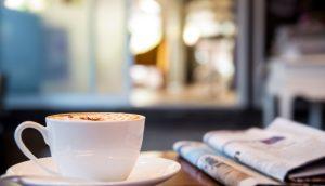 Kaffeetasse steht neben Zeitung auf einem Holztisch.