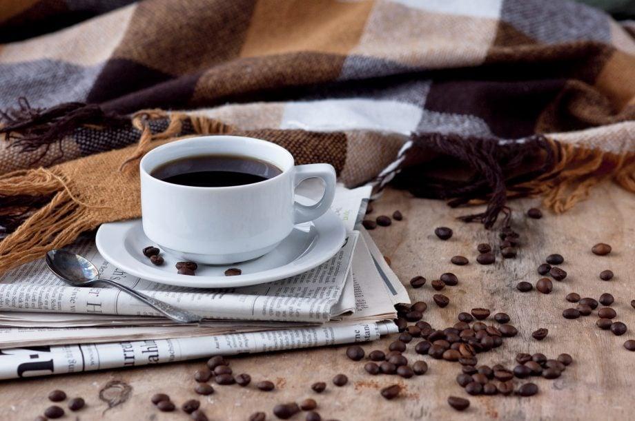 Eine weiße Kaffeetasse steht auf einem Stapel Zeitungen. Daneben liegen Kaffeebohnen und eine Wolldecke.