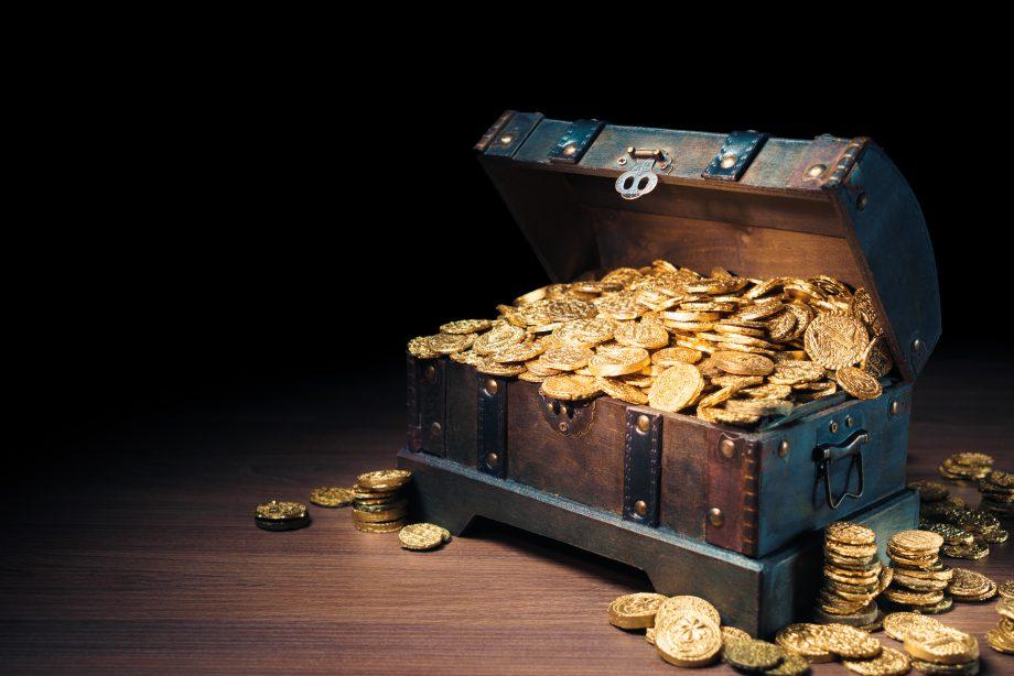 Truhe gefüllt mit Münzen steht auf Parkettboden