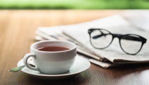 Eine Tasse Kaffee steht auf einem Holztisch neben einer Zeitung und eine Lesebrille.