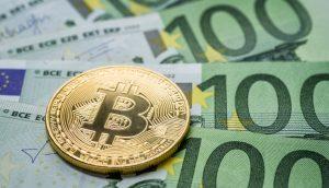 Bitcoin Münze liegt auf Euro Scheinen